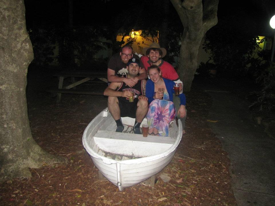 Four friends in a rusty boat behind a pub