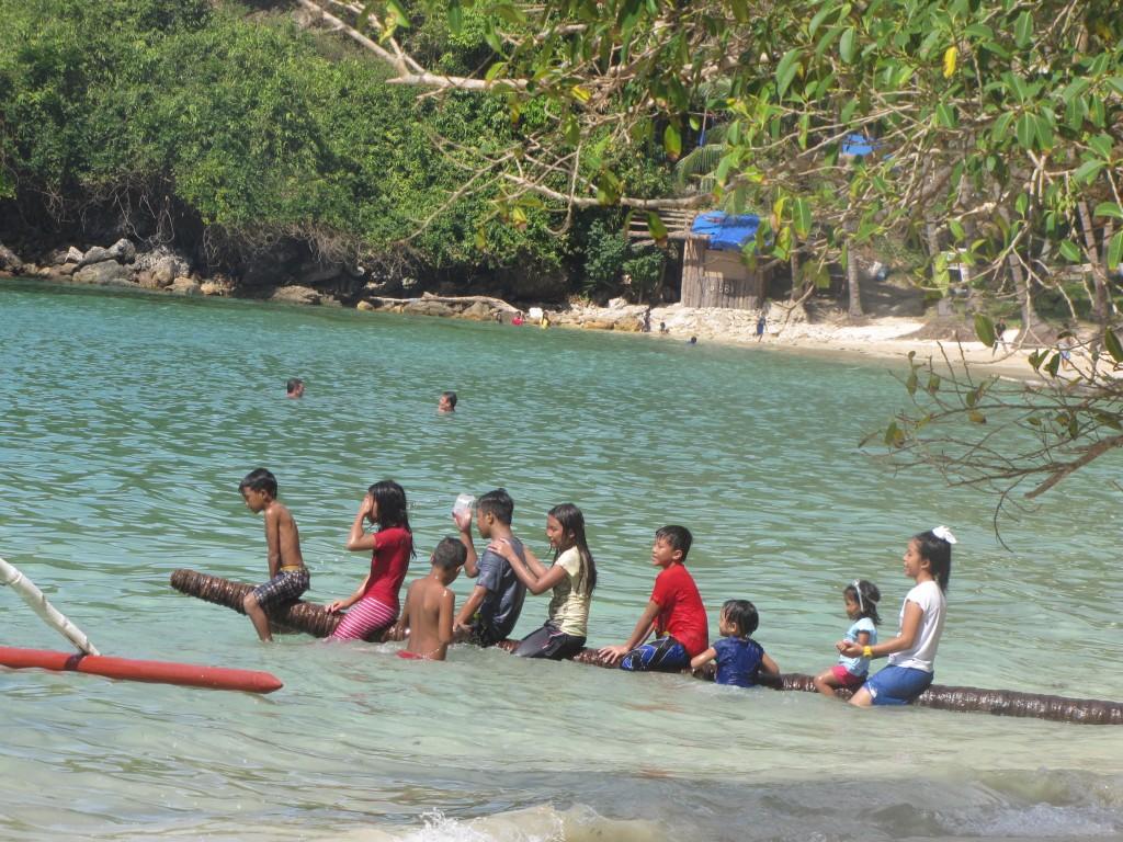 Local kids make their own entertainment with this log at a beach near El Nido